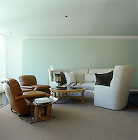 In this living room the large minimalist painting behind the sofa and armchairs is the focal point of the room