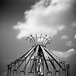 Monochrome Holga carnival image of Yoyo ride with clouds
