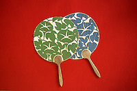 Flat uchiwa fans showcase traditional Japanese patterns against a red background.