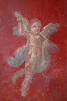 Detail of a cherub on a red background, fresco in the Fourth Style of Roman wall painting, 60-79 AD, in the large room adjoining the service room in the Fullonica di Stefanus, or Fullonica of Stephanus, a laundry in Pompeii, Italy. Pompeii is a Roman town which was destroyed and buried under 4-6 m of volcanic ash in the eruption of Mount Vesuvius in 79 AD. Buildings and artefacts were preserved in the ash and have been excavated and restored. Pompeii is listed as a UNESCO World Heritage Site. Picture by Manuel Cohen
