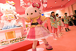 A staffer dressed in Hello Kitty outfit dances with staff at the opening of Hello Kitty's Kawaii (Cute) Paradise, a Hello Kitty theme store, in Tokyo, Japan on Thursday 21 October  2010. .Photographer: Robert Gilhooly