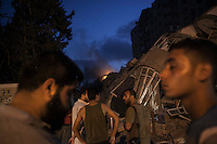 "August 23, 2014 - Gaza City, Gaza strip, Palestinian Territory: Palestinian men walk by the rubble of an apartment complex targeted by a warplane in Al-Zawayda neighborhood of central Gaza City as ""Protective Edge"" Israeli military operation continues in the Gaza strip. (Narciso Contreras/Polaris)"