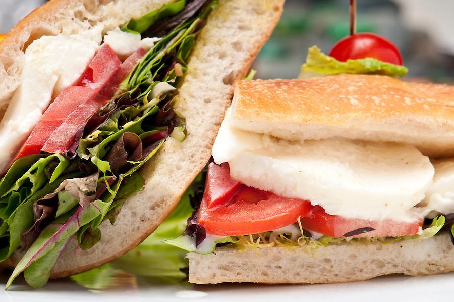 Close up of sandwich of mozzarella, lettuce and tomato.