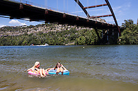 Summer finds two attractive female friends on vacation having fun floating inner tubes, talking at the Loop 360 Bridge Park Beach on Lake Austin.