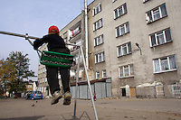 Chechen child on a see-saw in the back courtyard of the URiC Wolomin refugee centre, in Poland..On the right, the former hotel how give shelter to 130 refugee manly from Chechnya, but also from Byelorussia, and Pakistan..-For security reason, the face of the adult asylum seeker have been evicted of the photography..-For security reason, the names of the adult asylum seeker have been change. .-Article 9 of the Act of 13 June 2003 on grating protection on the Polish territory (Journal of Laws, No 128, it. 1176) personal data of refugees are an object of particular protection..-Cases where publication of a picture or name of asylum seeker had dramatic consequences for this persons and is family back in Chechnya. .Please have safety of those people in mind. Thank you.