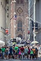 Groups of tourists in New York on Wall Street, with historic Trinity Church in the background, near the New York Stock Exchange in Friday, July 3, 2015.  Tourism in New York State in 2014 topped $100 billion for the first time.  It is the most visited state for overseas tourists for the 14th year in a row. (© Richard B. Levine)