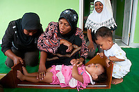 Indonesia, Sumatra, Aceh.  Muslim families gather at a clinic which provides women and children with education and health care.