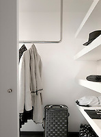In the dressing room there is a stainless steel clothes rail and a generous length of open shelving
