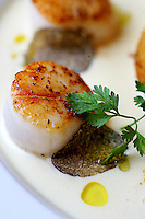Sea Scallops with Shaved Black Truffles. Diver scallops are flash-seared, served with Chablis cream sauce, crispy risotto cake, shaved black truffles and white truffle infused olive oil at Seastar Restaurant in Seattle.