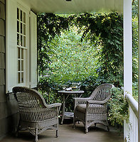 A pair of wicker armchairs at one end of a wisteria-clad veranda of a shingled house