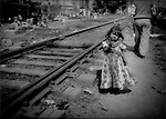 Untouchable (Dalit) girl from squatter family, that earns food money from rag 'recycling', plays in rail yard with trains coming and going all day, Delhi, India.