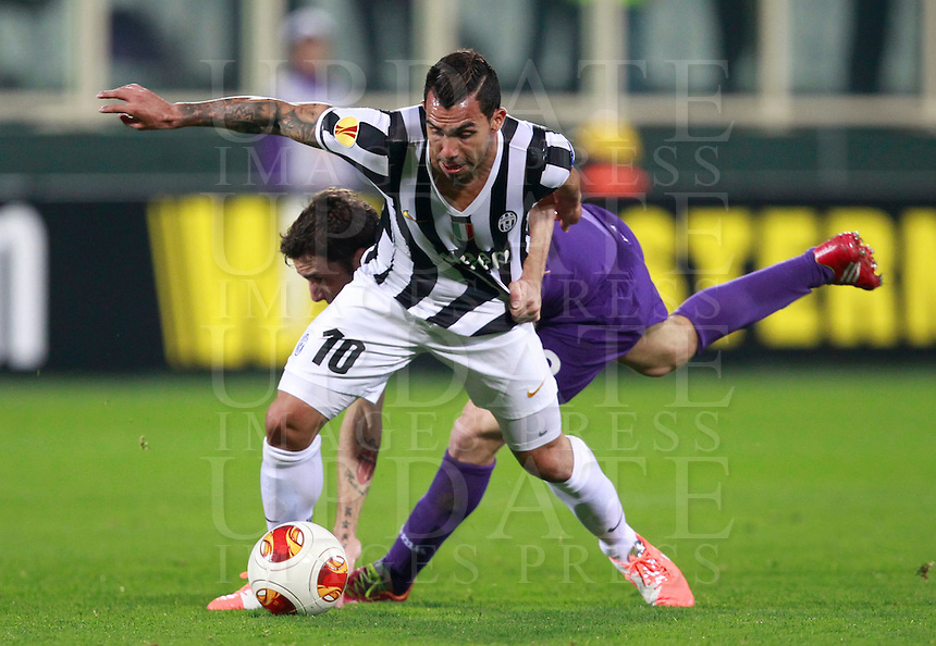 Calcio, ritorno degli ottavi di finale di Europa League: Fiorentina vs Juventus. Firenze, stadio Artemio Franchi, 20 marzo 2014. <br /> Juventus forward Carlos Tevez, of Argentina, foreground, and Fiorentina defender Gonzalo Rodriguez, of Argentina, fight for the ball during the Europa League round of 16 second leg football match between Fiorentina and Juventus at Florence's Artemio Franchi stadium, 20 March 2014. Juventus won 1-0 to advance to the round of eight.<br /> UPDATE IMAGES PRESS/Isabella Bonotto