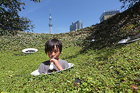 Kamon Nishino, aged 8, enjoys an ice-cream while playing in a park in Asakusa, with Skytree in the background. Tokyo, Japan. Sunday July 19th 2015