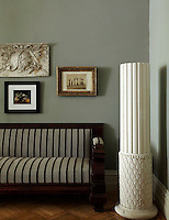 A column is paired with classically themed artwork and a carved sofa giving the living/dining area a strong classical aesthetic