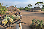 Christine Fatina, a United Methodist, cuts a pineapple she has harvested  on her family's farm in Pisak, Southern Sudan...
