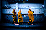 Buddhist monks pass through Bangkok's red-light district on their morning walk in Bangkok, Thailand, Southeast Asia. Each morning, monks must walk from their monasteries to meet and pray for lay Buddhists, who place food and money in the alms bowls carried by the monks.