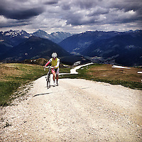 A lone cyclist walks the final, steep pitches near the summit of Plan de Corones ( Kronplatz), in the heart of the Dolomites, Südtirol (South Tyrol), Italy. The dirt track ascends to the summit of the ski area, and reaches 24 percent at its maximum. The 2010 Giro d'Italia finished atop the climb during a mountain time trial.