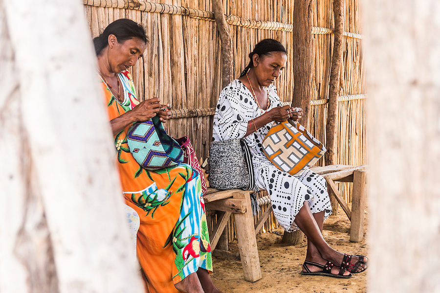 "Two Wayuu indigenous women knitting ""mochilas"", or traditional handbags, in a ""rancheria"", or rural settlement.  Knitting, crocheting and weaving are fundamental to the social and economic lives of Wayuu women in La Guajira, Colombia."