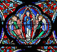 2 angels lift Mary, in a mandorla of glory, to heaven, the Assumption of the Virgin, from the Glorification of the Virgin stained glass window, in the nave of Chartres Cathedral, Eure-et-Loir, France. This window depicts the end of the Virgin's life on earth, her dormition and assumption, as told in the apocryphal text the Golden Legend of 1260. Chartres cathedral was built 1194-1250 and is a fine example of Gothic architecture. Most of its windows date from 1205-40 although a few earlier 12th century examples are also intact. It was declared a UNESCO World Heritage Site in 1979. Picture by Manuel Cohen