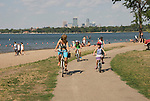 Minnesota, Twin Cities, Minneapolis-Saint Paul: Recreation at the south end of Lake Calhoun, with the Minneapolis skyline in the background.  Family bicycling..Photo mnqual273-75193..Photo copyright Lee Foster, www.fostertravel.com, 510-549-2202, lee@fostertravel.com.