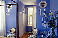 In a pretty lavender-blue bedroom a pair of sconces have been arranged with perfect symmetry on either side of the entrance while a collection of coloured glass on a side table adds a deeper note of blue