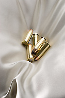 Bullets laying on satin pillow