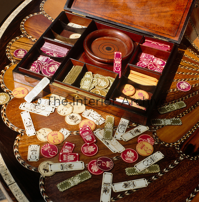 Pieces of a Victorian game are scattered on an intricately inlaid table