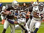 Denver Broncos defensive back Sam Brandon (42) tackles Oakland Raiders wide receiver Doug Gabriel (85) on Sunday, November 30, 2003, in Oakland, California. The Broncos defeated the Raiders 22-8.