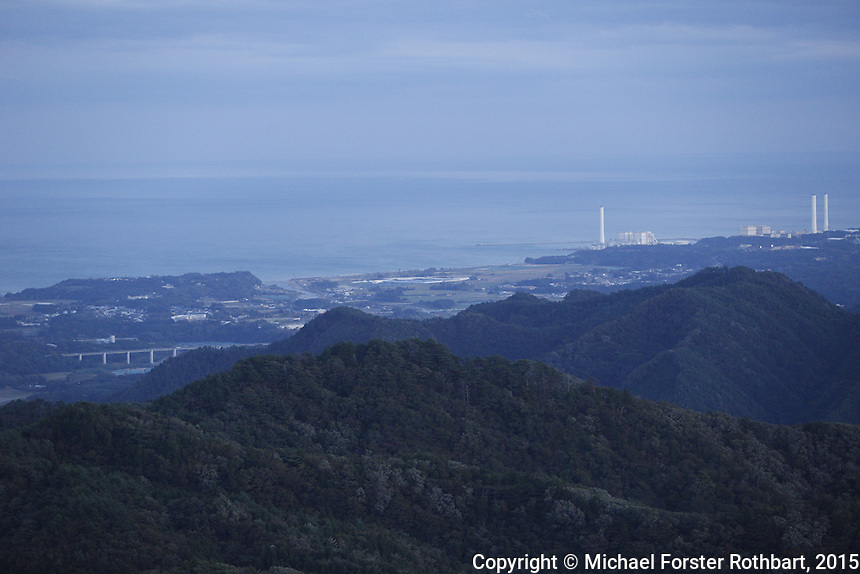 View from Mount Okura at dusk. Mt. Okura is a 1950-foot peak in the Fukushima Exclusion Zone, 8 miles from the destroyed Fukushima Daiichi nuclear power plant. The panoramic view from the top includes power plants in three adjacent coastal towns: Fukushima Daiichi to the northeast in Tomioka, Fukushima Daini 5.25 miles to the east in Naraha, and Hirono Power Station, a coal-generation plant 8.5 miles to the southeast. Much of Naraha is visible, including the junior high, the town hall and the Kido river, as well as the rest of the Abukuma range to the west.<br /> <br /> &copy; Michael Forster Rothbart Photography<br /> www.mfrphoto.com &bull; 607-267-4893<br /> 34 Spruce St, Oneonta, NY 13820<br /> 86 Three Mile Pond Rd, Vassalboro, ME 04989<br /> info@mfrphoto.com<br /> Photo by: Michael Forster Rothbart<br /> Date:  10/13/2015<br /> File#:  Canon &mdash; Canon EOS 5D Mark III digital camera frame B22987