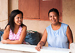 Sampaloc buri weaver Mercy Bala (on right) chats with her daughter in front of their home on the outskirts of town.  Mercy produces many of the wine bags sold at wineries across Virginia.