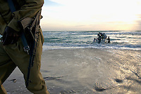 A military guard leaves a fishing boat after helping it into the Indian Ocean in the coastal village of Eyl.