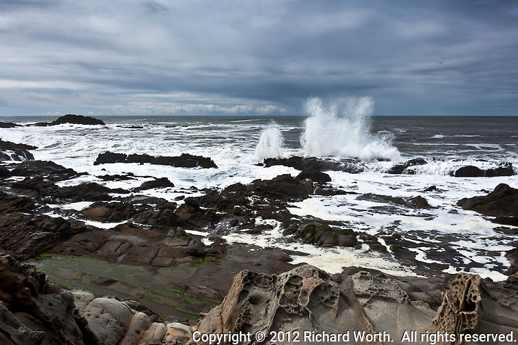 A wide ocean view from a rocky beach with tafoni formations as a wave crashed into a rocky outcrop off shore.  Bean Hollow State Beach south of San Francisco on the California coast.