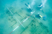 Three SCUBA divers record a 17th century shipwreck in Panama. (Model Released)
