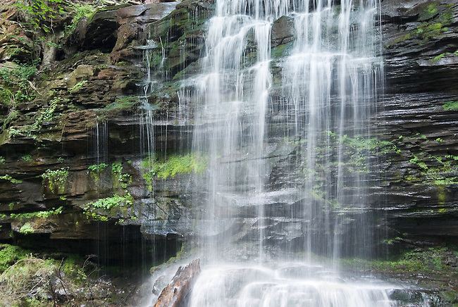 Waterfall curtain close-up flowing over black layered rock captures the essence of water in the woods, natural beauty at Ricketts Glen State Park near Williamsport, Pennsylvania.