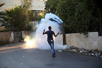A Palestinian protester uses a slingshot to throw back a tear gas canister during clashes with Israeli security forces earby the Jalazoun refugee camp and the Jewish settlement of Beit El, north of Ramallah, after a demonstration in reaction to the death of a Palestinian toddler who was burned in an arson attack by suspected Jewish settlers on two homes in the occupied West Bank on July 31, 2015. Photo by Shadi Hatem