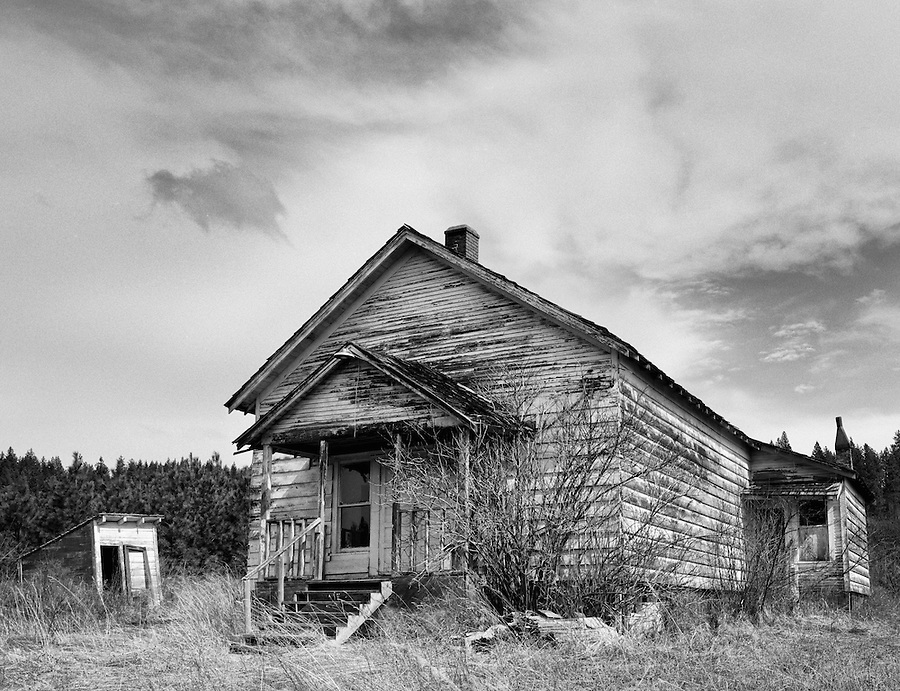 A decrepit farmhouse and small shed sit in the eerie silence.