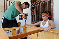Volunteers constructing desks for a home school at an orphanage supported by EDV, Port-au-Prince, Haiti. EDV is committed to affecting permanent change in disaster-affected communities worldwide. Their role is to facilitate personal connections between volunteers and the survivors of disasters.  The charity is based on a proven model developed by several landmark organisations that have paved the way for citizens to become disaster volunteers. These landmark organisations have shown that supposedly ordinary people working together with the guidance of knowledgeable leaders can make an extraordinary difference in the lives of those affected by disaster..EDV believe that to provide meaningful relief and reconstruction assistance to disaster affected communities they have to do more than reconstruct buildings. They need to understand and address the factors that made a community vulnerable to the disaster in the first place. The charity's work is organised with these factors in mind so that they can affect change that far outlives their presence..EDV believes that survivor motivation is essential to the recovery of any disaster-affected community. Their operations will always be predicated on the idea that survivors may be traumatised, but they are not helpless. With this in mind, EDV encourages host communities to direct their own recovery. EDV believe that this empowerment is essential in helping survivors feel a renewed sense of control over their lives which will, in turn, help overcome the feelings of hopelessness that can follow a disaster and inhibit long term recovery. EDV also believe that social cohesion is of primary importance in any disaster-affected area. No amount of bricks or mortar will bring about sustainable improvement if communities fail to come together or are disrupted by relief efforts. Therefore, their operations will always aim to foster communication and cooperation within and between the communities they serve.
