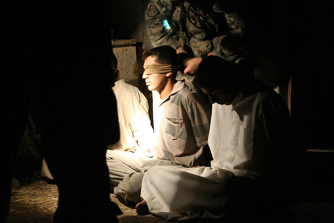A soldier with Company B, 3rd Battalion, 509th Infantry Regiment ties a blindfold over the eyes of a young man suspected of planting bombs against U.S. forces near Sayafiyah, Iraq, south of Baghdad.  Aug. 16, 2007. DREW BROWN/STARS AND STRIPES