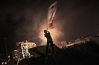 In this Tusday, Jun. 11, 2013 photo, a protester waves a flag on a barricade as clashes continue during night in Taksim Square after the anti-riot police entered early in the morning to take back the control of the square, protesters were gathering by thousands to protect Gezi park during the ongoing turmoil in Istanbul,Turkey. (Photo/Narciso Contreras).