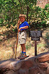 Young hiker (age 4) with walking stick standing next to the Emerald Pools trail sign in Zion Canyon, Zion National Park, Utah