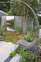 Curved chair and sinuous water feature in sophisticated garden &amp; patio, with wall, birch trees, plantings, providing a sense of movement and flow