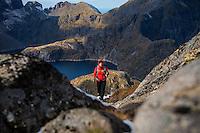 Female hiker on hiknig trail near the summit of Munken, Moskenesøy, Lofoten Islands, Norway