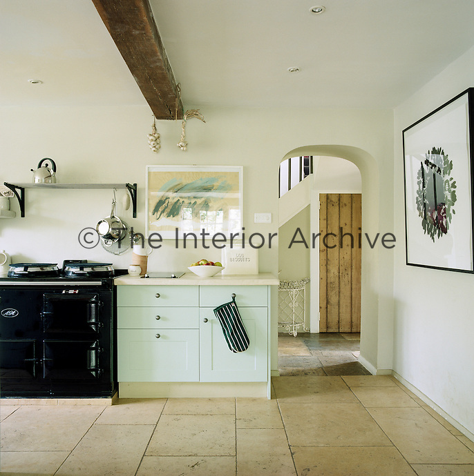 Pale stone flags cover the floor of the kitchen where there is also plenty of wall space to display large framed contemporary prints and paintings