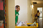 Aaron Musser, a Go-Green Move-In volunteer, pushes a cart of a students belongings into Atkinson Hall on South Green on Friday, August 19, 2016. © Ohio University / Photo by Kaitlin Owens