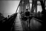 Bicycle rider coming to market in Hanoi on the Long Bien Bridge, Hanoi which was repeatedly bombed by American planes during the until American POW ?s were set  to rebuilding it, Vietnam..