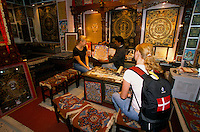 Danish tourist in a Thangka shop in Kathmandu. The lamas who paint thangkas use painting as a form of spiritual education and can spend up to 9 months on each canvas. Thangkas are seen hanging in every temple, monastery and family shrine in Tibet and Nepal.
