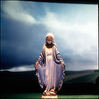 Glowing Virgin Mary figurine with landscape background