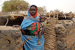 A woman and baby displaced by violence in the Darfur region of Sudan. They are living in the remnants of what was once a thatched roof house, but which was burned in an attack by pro-government Arab militias and Sudanese government troops.