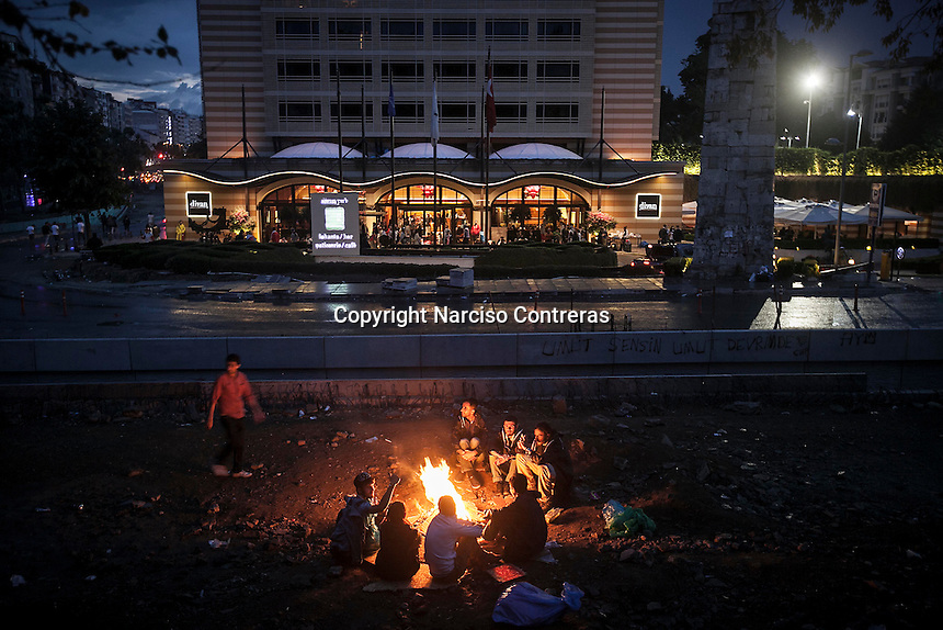 Protesters gather around fire as down rises up in Gazi park of Taksim Square during a 24/7 masive rally against the turkish government in Istanbul, Turkey.