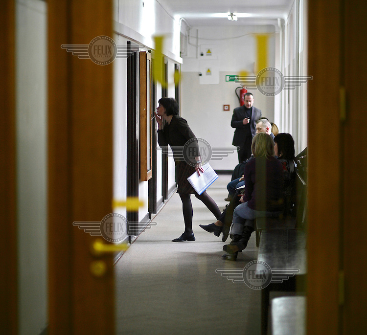 A woman is looking at the list of the day's trials, while waiting for a divorce trial at a court in Warsaw.